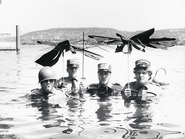 Drei Offiziere stehen im Wasser und halten kaputte Schirme in die Höhe.