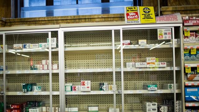 Halbleeres Regal mit Zigarettenpackungen.