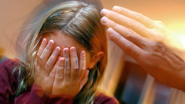 Mädchen wird geschlagen, hält Hände vors Gesicht.