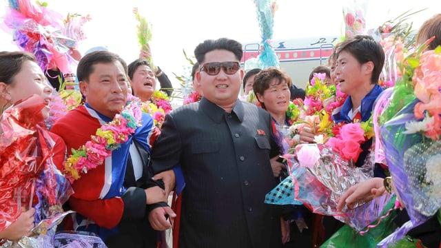 Dikator Kim Jong Un in einer jubelnden Menschenmenge.