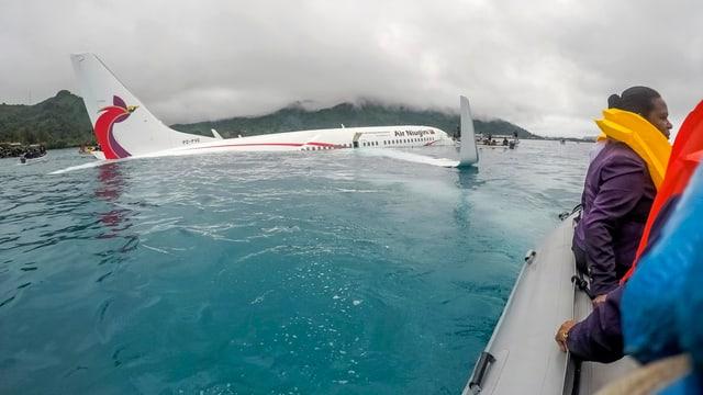 Flugzeug im Wasser, daneben Rettungsboote.