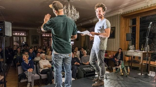 Zwei Männer stehen auf der Bühne - Publikum lacht