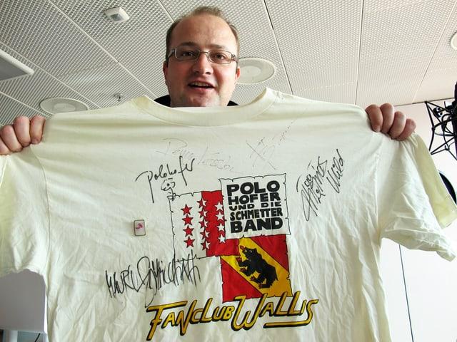 Michael Brunner streckt das signierte Fanclub-T-Shirt in Richtung Kamera.