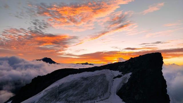 Sonnenaufgang auf dem Allalinhorn. Links und rechts unten brodelnde Quellwolken, darüber orange hohe Wolken.