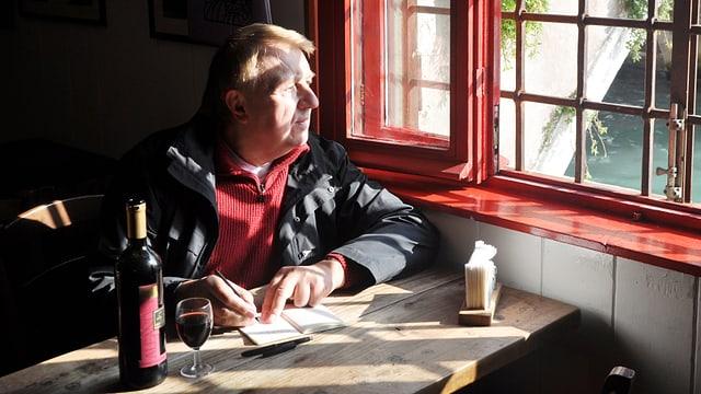 Hanns-Josef Ortheil sitzt mit einem Glas Wein und Notitzbuch an einem Tisch und schaut aus dem Fenster.