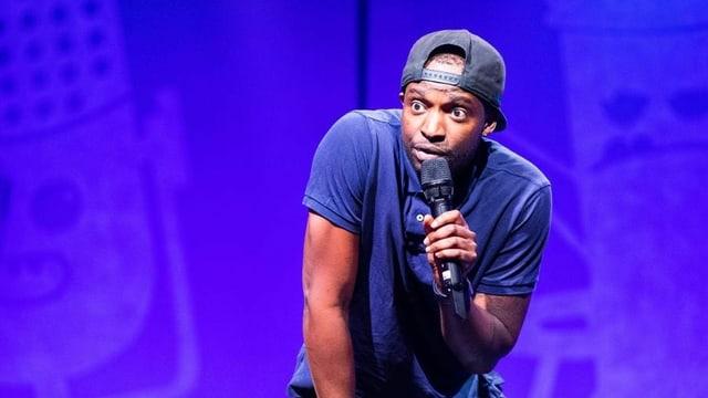 Charles Nguela steht bei der Comedy Talent Show auf der Bühne, hat ein Mikrofon in der Hand und schaut ausdrucksvoll in das Publikum.