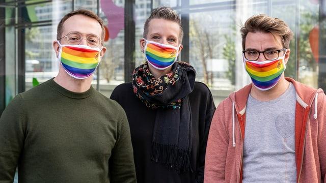 drei Menschen tragen Mundschutzmasken in Regenbogenfarben