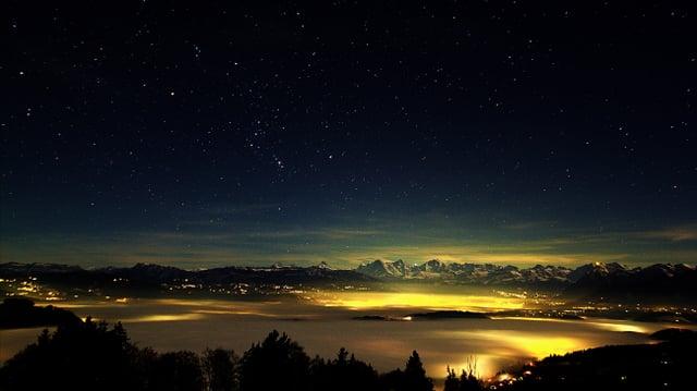 Nächtlicher Blick von der Bütschelegg auf das Nebelmeer, dahinter die Berner Alpen.