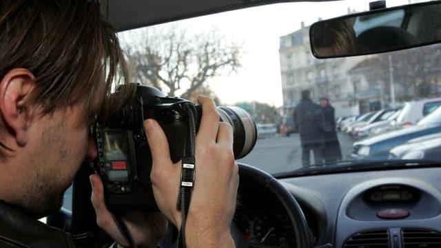 Ein Mann sitzt mit einer Kamera in einem Auto und fotografiert ein Paar.