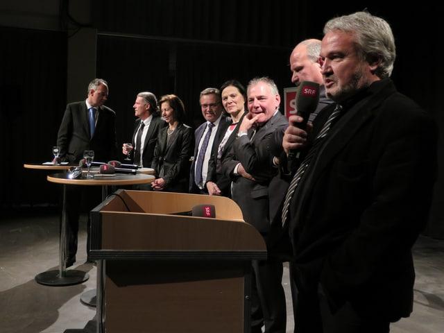Alle Politiker stehen in einer Reihe nebeneinander, einer spricht ins Mikrofon.