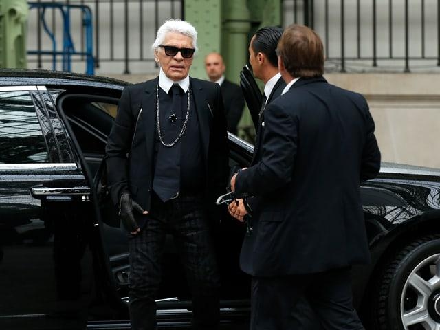 Karl Lagerfeld steigt aus dem Auto aus.
