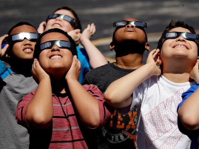 Schulklassen verfolgen gespannt den Himmel.