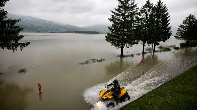 Ein Motorrad fährt auf einer vom Lauerzersee überfluteten Strasse.