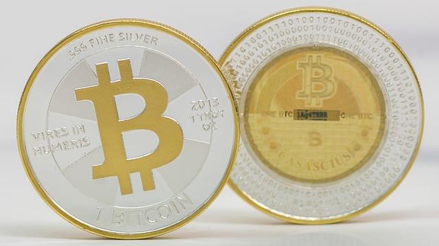 Ein aufgeklappter Laptop, darauf sieht man viele Münzen mit einem «B» darauf.