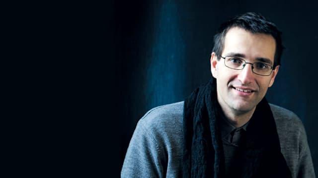 Porträt von Josef Schovanec vor schwarzem Hintergrund.