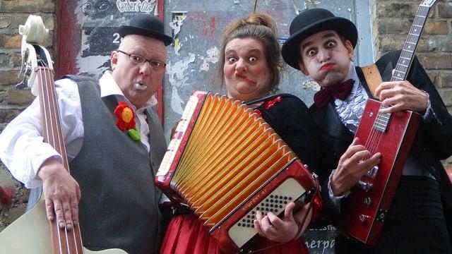 Zwei Männer und eine Frau, geschminkt und mit Instrumenten.