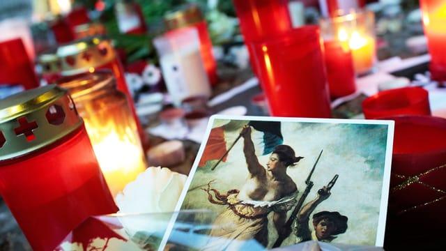 Neben den Trauerkerzen liegt ein Bild der Marianne.