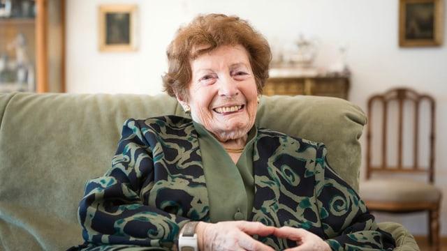 Eine ältere Dame sitzt auf dem Sofa.