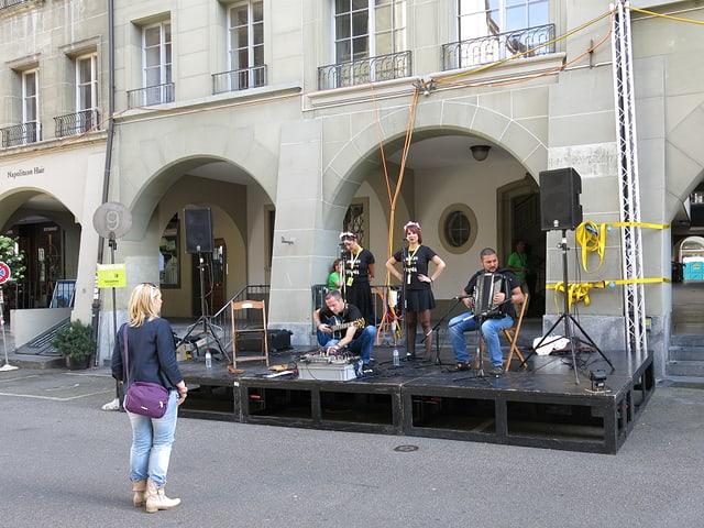 Vier Musiker auf einer Bühne, eine einzige Frau steht davor