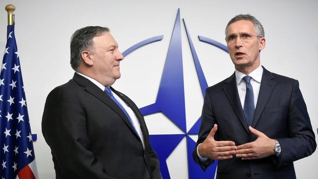 Pompeo und Stoltenberg vor einer US-Flagge und einem Nato-Emblem.