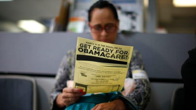 Eine Person studiert einen Obamacare-Flyer.