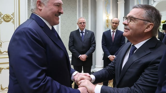 René Fasel und Alexander Lukaschenko schütteln Hände bei einem Treffen.
