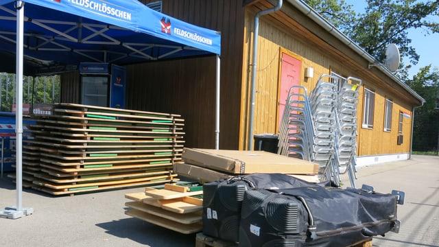 Holzbänke und -tische liegen vor dem Clubhaus des FC Wyler