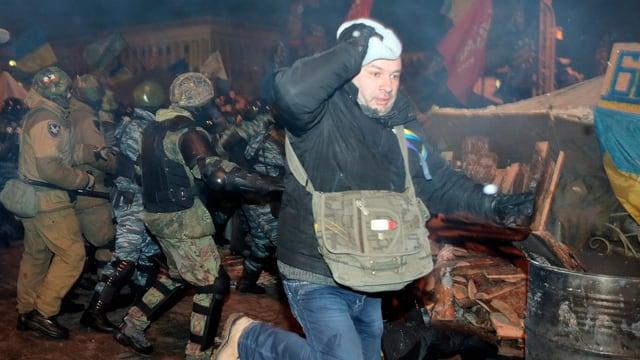 Ein Demonstrant flieht vor der anrückenden Bereitschaftspolizei