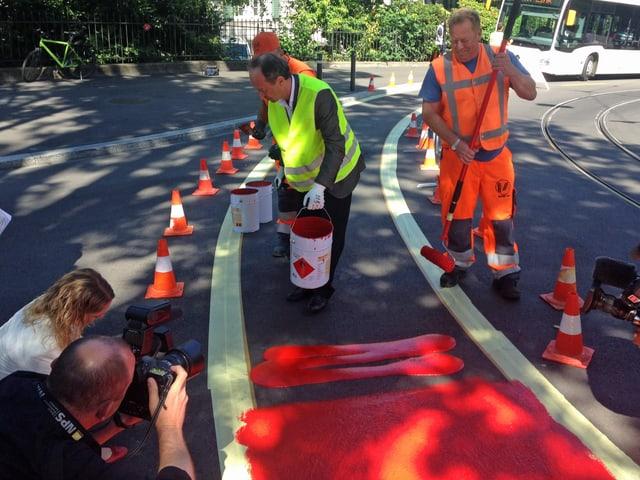 Stadtrat Richard Wolff bückt sich zu den roten Farbtöpfen, um einen Velostreifen an der Leonhardstrasse einzufärben.