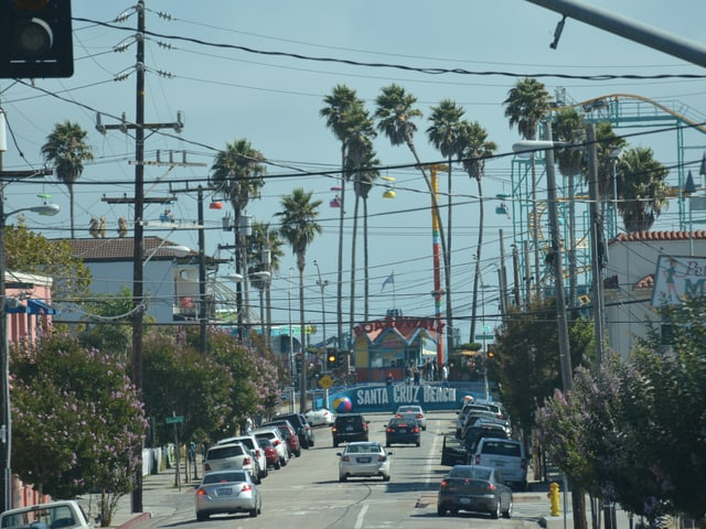 """Eine Strasse in Santa Cruz, Stromleitungen hängen über die Strasse, am Ende kann man ein blaues Schild erkennen, auf dem """"Santa Cruz Beach"""" steht, dahinter hohe Palmen."""