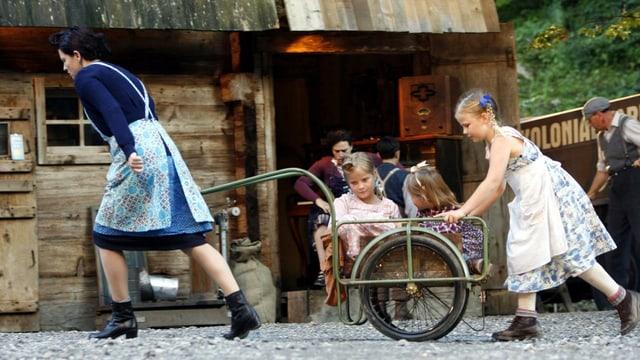 Szene aus dem «Schwarzen Tanner», aufgeführt im Freilichtmuseum Ballanberg: Eine Frau zieht einen Velo-Anhänger, darin zwei Mädchen, ein drittes Mädchen stösst den Anhänger.