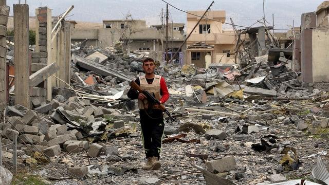 Ein Miliziönär patroulliert in einem zerstörten Viertel von Sindschar.