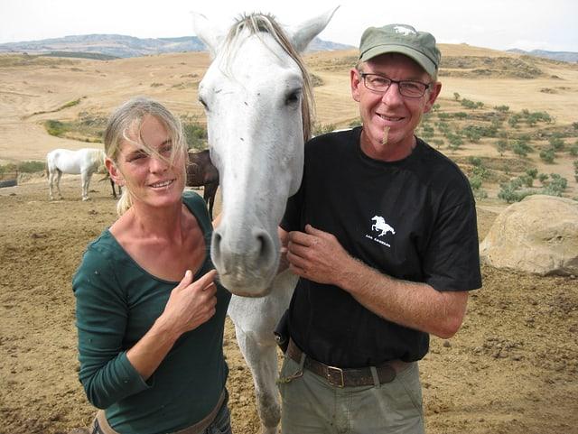 Ein Porträt von einer Frau und einem Mann. Zwischen ihnen steht ein weisses Pferd.