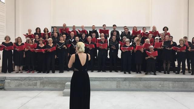 Ils dus chors en acziun cun la dirigenta dal chor Pontanima, Alma Aganspahic.