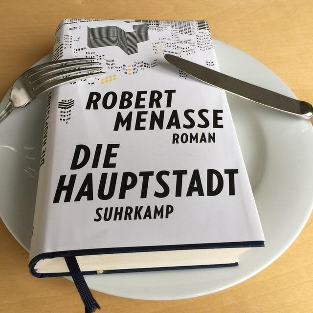 Der Roman  «Die Hauptstadt» von Robert Menasse liegt auf einem weissen Teller. Messer und Gabel angelehnt.