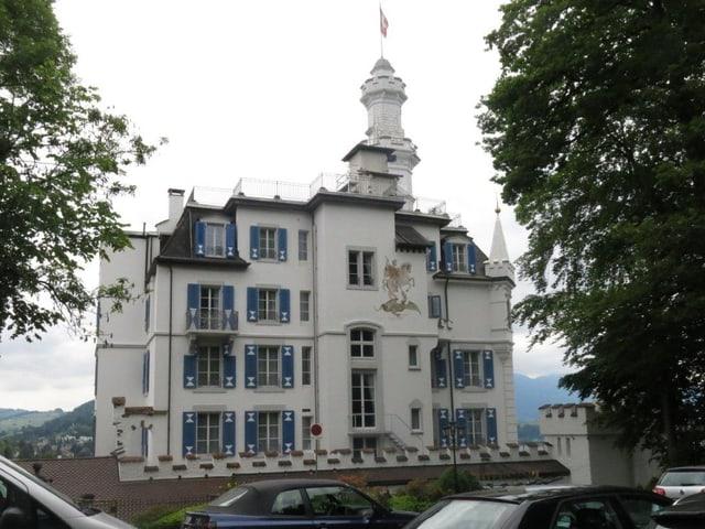 Blick vom Parkplatz aus auf die weisse Fassade mit blauen Fensterläden.