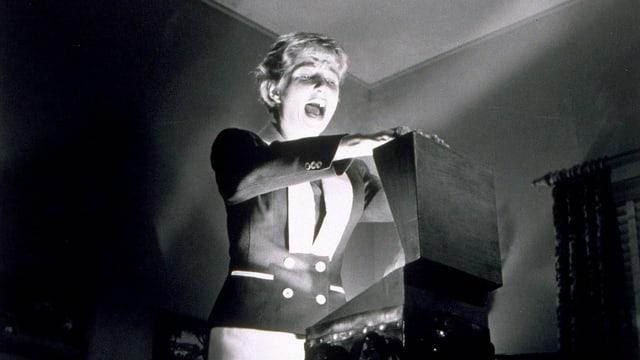 Ein Still aus einem Schwarz-Weiss-Film: Eine Frau öffnet einen Koffer, aus dem Lichtstrahlen kommen.