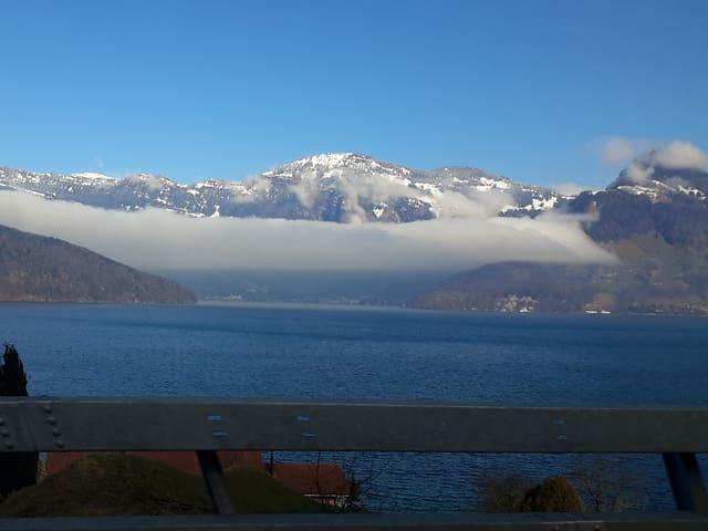 Am Fuss eines verschneiten Berges ist ein Wolkenband zu sehen. Darüber ist der Himmel blau.