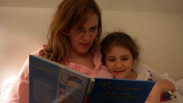 Daniela liest Alicia eine Gutenachtgeschichte vor.