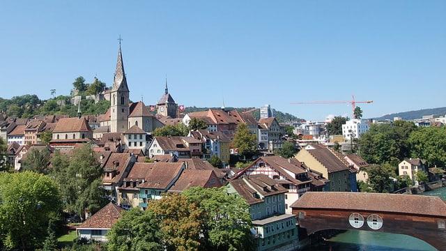 Bild von der Altstadt in Baden, mit der Brücke und dem Kirchturm. Im Hintergrund ist ein Baukran zu sehen.