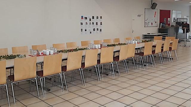Ein grosser Tisch mit vielen Stühlen und Kaffeetassen darauf