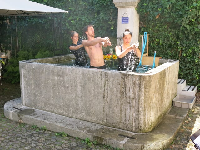 Drei Menschen planschen im Brunnen.