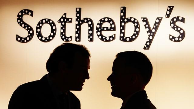 Im Hintergrund steht Sotheby's. Vorne diskutieren zwei Männer. Man sieht nur ihre Schatten.