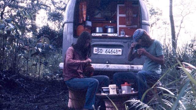 Ein junges Paar isst zusammen vor dem VW-Bus im Wald.