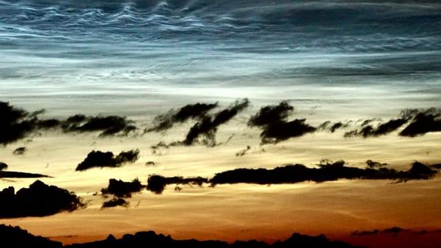 Abendstimmung mit dunklen Quellwolken und silbernen Leuchtenden Nachtwolken.
