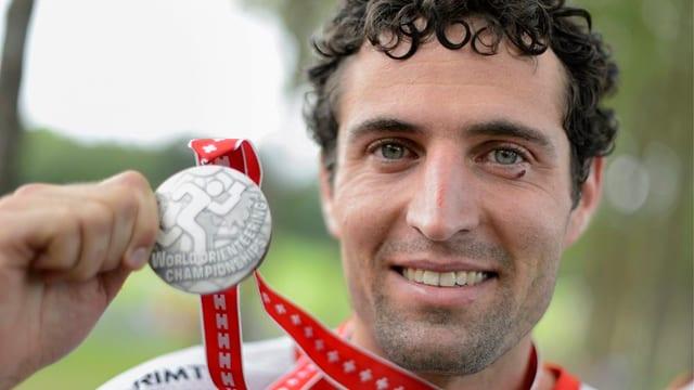 Matthias Merz zeigt seine Silbermedaille in die Kamera