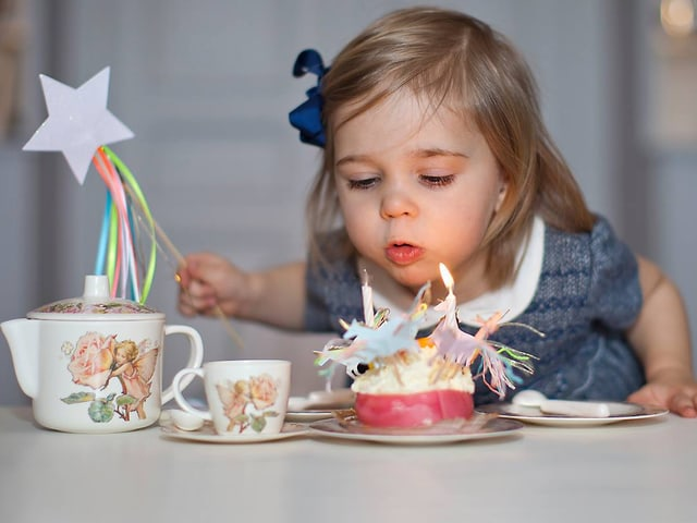 Ein Mädchen bläst einen Geburtstagskuchen, auf dem zwei Kerzen stecken, aus.