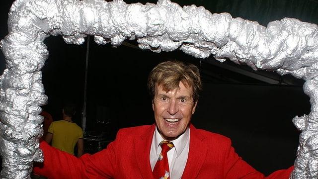 Freddy Breck hält einen überdimensionalen silbernen Fotorahmen in den Händen.