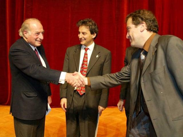 """Marc Rich, links, gratuliert den Tessiner Kino Festivalorganisatoren """"Castellinaria"""" Brenno Martignoni, Mitte, und Stelio Righenzi, rechts, zum Doron Preis 2002"""