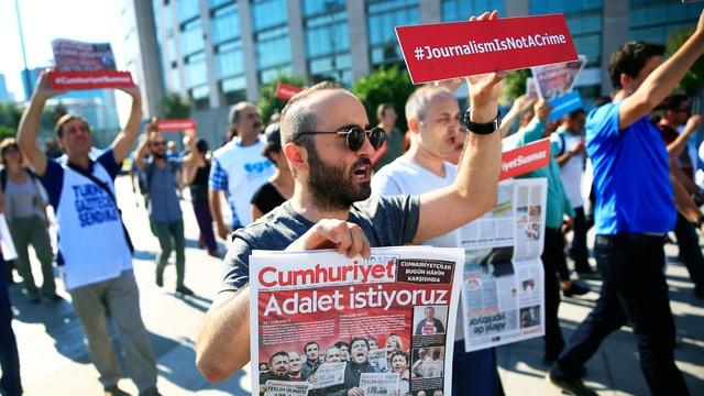 Menschen demonstrieren in Istanbul gegen die Verhaftung von Journalisten.